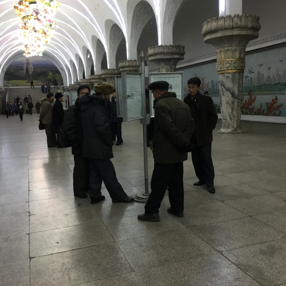 Reading the days news in the Pyongyang Metro Station